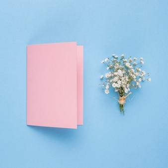 Invitación de boda rosa junto a flor ornamental.