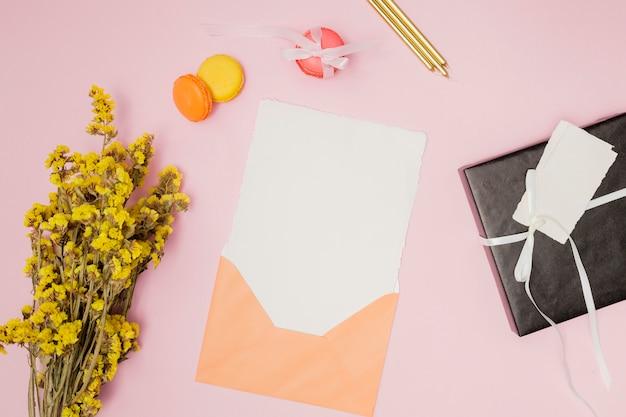 Invitación de cumpleaños naranja maqueta junto a artículos de cumpleaños