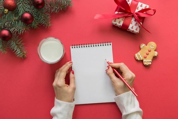 Invitación de navidad con leche, galletas, pan de jengibre en rojo. vista superior y espacio para su texto. endecha plana.