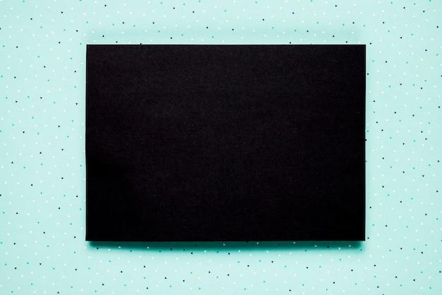 Invitación negra sobre fondo verde azulado
