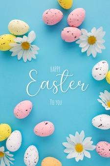 Invitación de pascua con huevos y margaritas sobre un fondo azul.