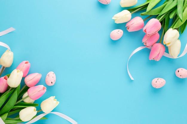 Invitación de pascua con tulipanes sobre un fondo azul con espacio de copia