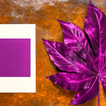 Invitación púrpura y hoja en la mesa