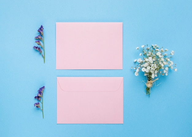 Invitaciones de boda planas junto a flores.