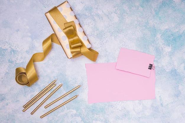Invitaciones rosas con suministros de cumpleaños sobre fondo de mármol.