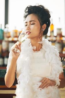 Invitada asiática disfrutando de copa de champán en la fiesta en el bar