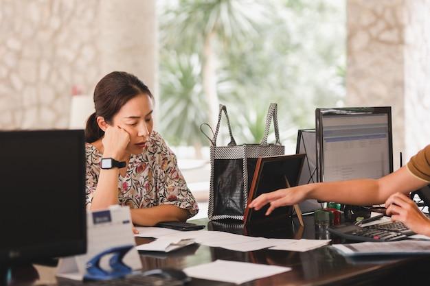 Invitada femenina revisando los documentos del hotel en la recepción