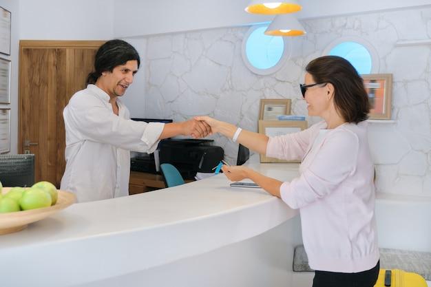 Invitado en el hotel, recepcionista hombre saludando mujer