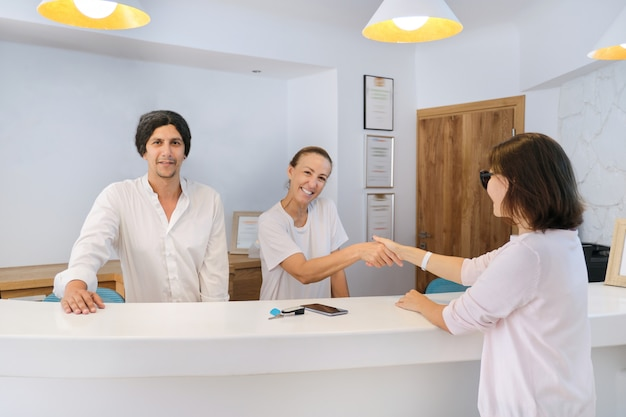 Invitado en el hotel, recepcionistas hombres y mujeres saludando a mujer