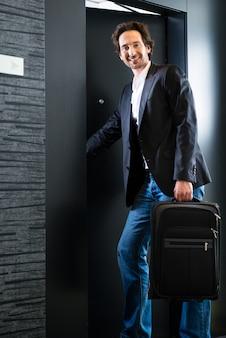 Invitado joven con equipaje entrando en la habitación del hotel