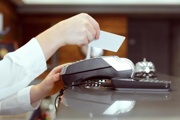 Invitado en recepción del hotel pagando con cheque durante el check-in