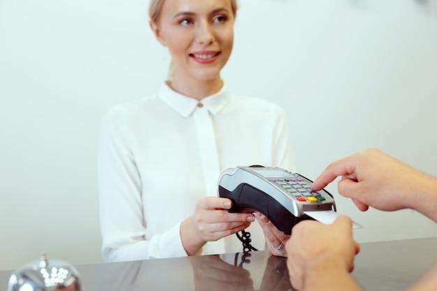 Invitado en la recepción del hotel pagando con cheque durante el check-in