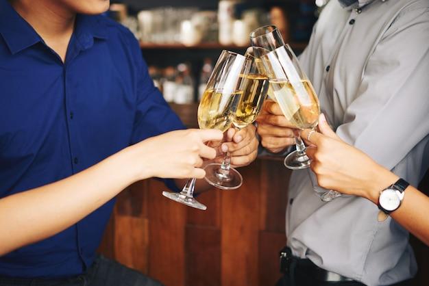 Invitados de fiesta irreconocibles que animan con champán en el bar