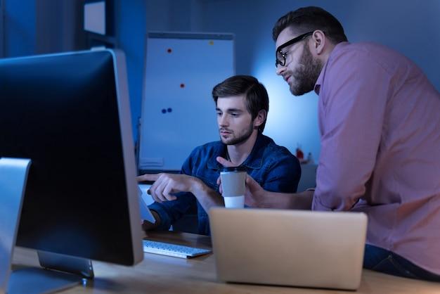 Involucrado en el trabajo. programadores serios, inteligentes y concentrados que se sientan juntos y buscan la información mientras trabajan juntos en un proyecto