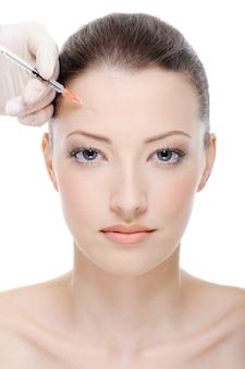 Inyección de botox en la frente femenina.