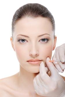 Inyección de botox en labios femeninos.