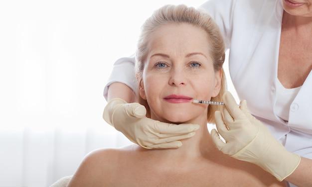 Inyección de botox en el rostro femenino