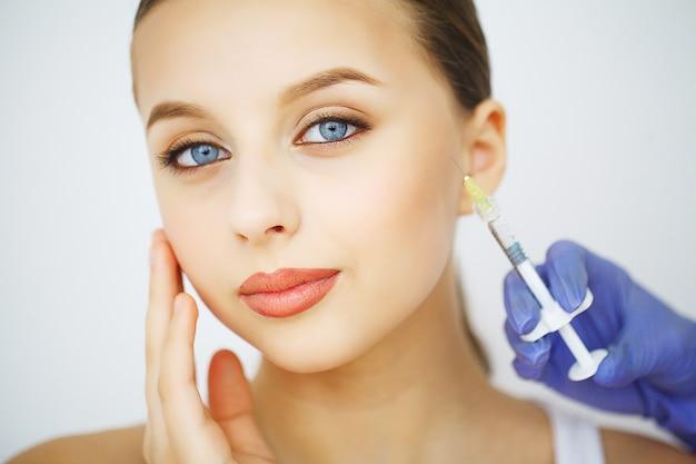 Inyección de cirugía plástica de labios en la cara de una mujer joven