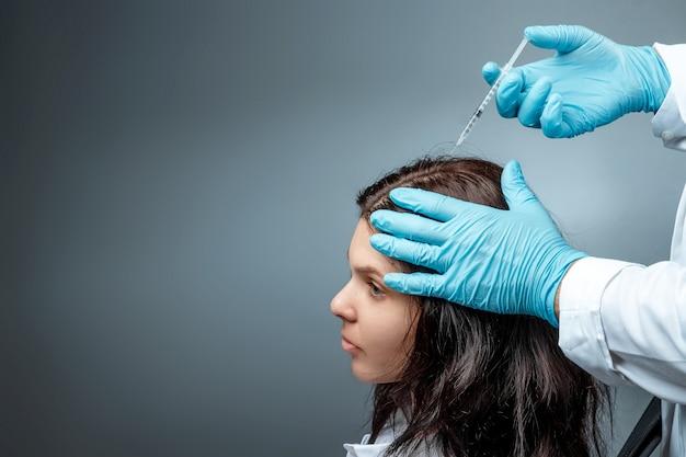 Inyección para el crecimiento del cabello, las manos del doctor krupnypy lan hacen una inyección, una inyección en la cabeza de una niña por pérdida de cabello. salud, cuidado del cuerpo, estilo de vida.