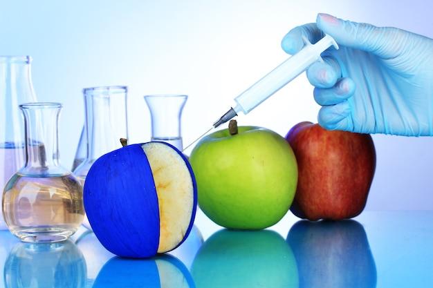 Inyección en manzana sobre fondo azul.