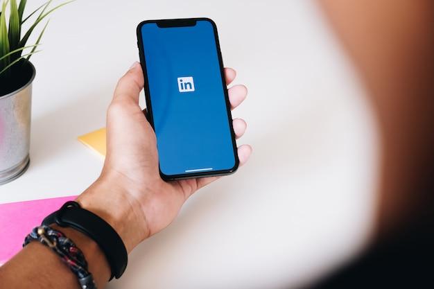 Un iphone xs con la aplicación linkedin en la pantalla. linkedin es una aplicación para compartir fotos para teléfonos inteligentes.