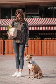 Ir a comprar comida con un perro entrenado. joven mujer bonita con cachorro pitbull terrier tiene bolsa de papel de comestibles en frente del mercado o tienda de verduras.
