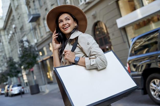 Ir de compras nos hace felices joven hermosa mujer emocionada con sombrero con bolsa de compras hablando sobre