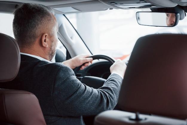 Ir a la reunión vista desde atrás del empresario senior en ropa oficial conduciendo un automóvil nuevo y moderno
