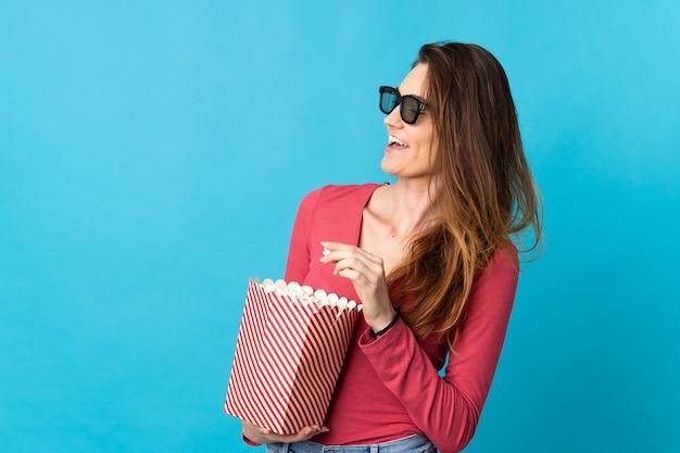 Irlanda joven mujer aislada sobre fondo azul con gafas 3d y sosteniendo un gran balde de palomitas de maíz