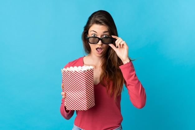 Irlanda joven mujer aislada sobre fondo azul sorprendido con gafas 3d y sosteniendo un gran balde de palomitas de maíz