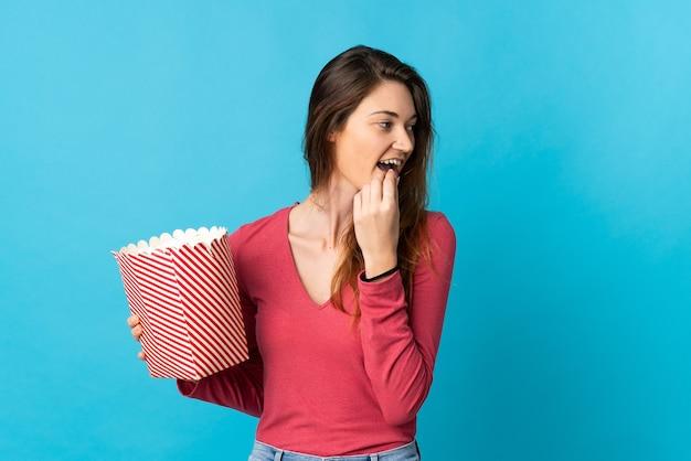 Irlanda joven mujer aislada sobre fondo azul sosteniendo un gran balde de palomitas de maíz