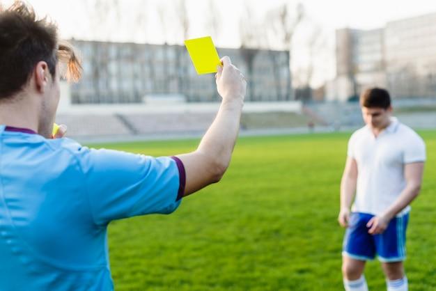 Irreconocible árbitro mostrando tarjeta amarilla