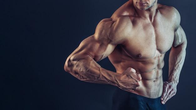 Irreconocible fuerte atlético sexy musculoso hombre equilibrado, mostrando bíceps y delts sobre fondo negro