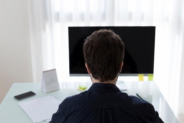 Irreconocible hombre navegando por la computadora en la oficina