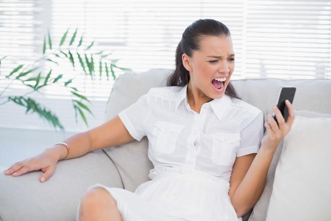 Irritada mujer en vestido blanco gritando en su teléfono inteligente