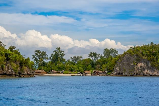 Isla en indonesia. raja ampat. varias cabañas tradicionales en la orilla entre las rocas y la playa