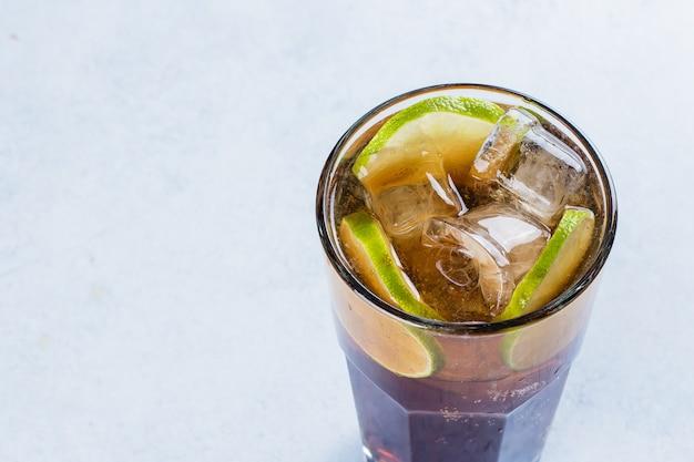 Isla larga con hielo y cal en la tabla ligera del fondo. cóctel de té helado