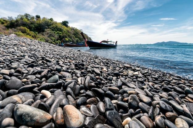 Isla de piedra negra con barco de madera en la costa en el mar tropical