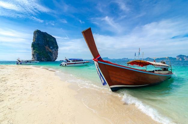 Isla de poda barco de madera estacionado en el mar, playa blanca en un cielo azul claro