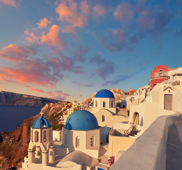 Isla de santorini en grecia, iglesia local en el pueblo de oia en una puesta de sol