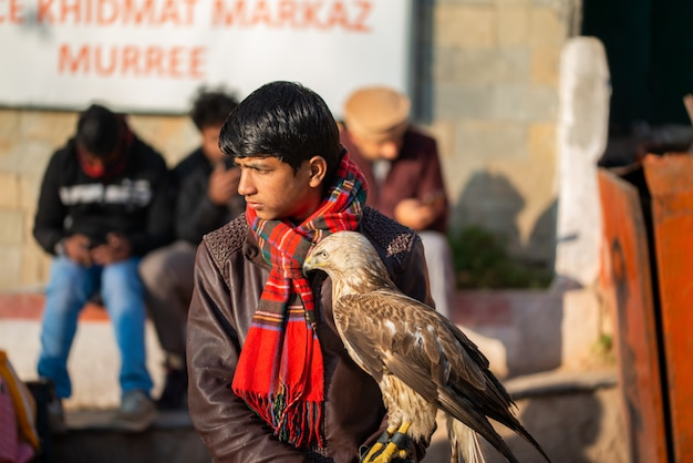 Islamabad, territorio de la capital de islamabad, pakistán - 05 de febrero de 2020, un niño está sentado junto a la carretera con su halcón entrenado.