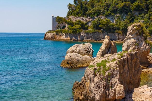 Las islas rocosas se encuentran en las aguas azules del mar adriático. grandes piedras se encuentran en el medio del mar, no muy lejos de las montañas verdes y el castillo colgante sobre el agua del mar.