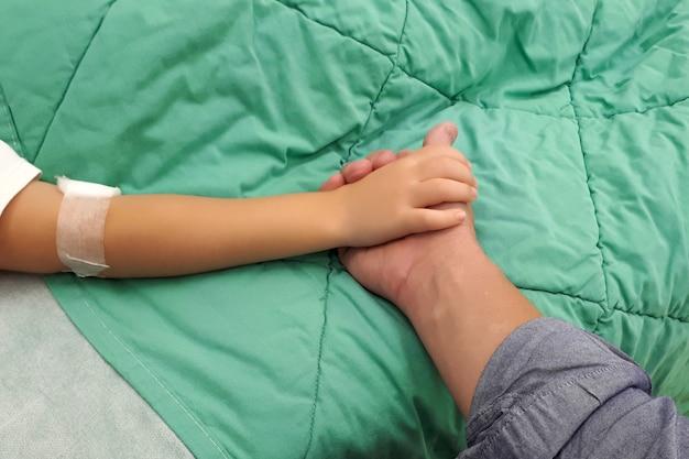 Iv goteo en mano niño en una cama de hospital
