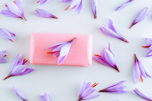 Jabón de azafrán y muchas hermosas flores de azafrán púrpura sobre blanco