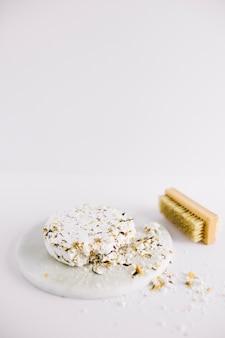 Jabón blanco quebrado en el tablero blanco cerca del cepillo en el fondo blanco
