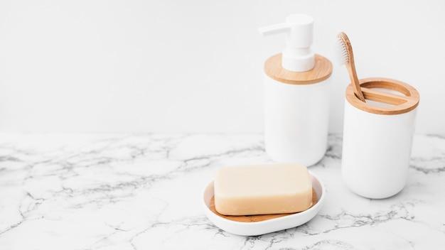 Jabón; botella cosmética y pincel sobre superficie de mármol