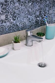 Jabón y cepillos de dientes cerca del grifo