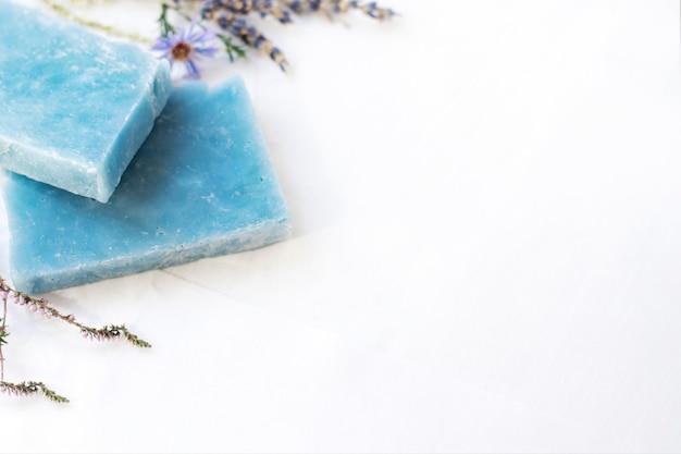 Jabón cosmético natural con minerales en una pared blanca con espacio de copia