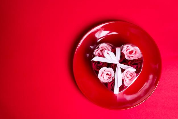 Jabón decorativo en forma de rosas en un plato.