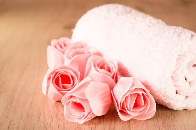 Jabón en forma de rosas y una toalla sobre un fondo de madera